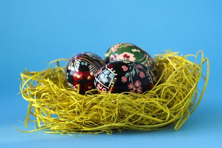 Three decorated Easter eggs lie in a nest of hay on a blue background. Ukrainian Easter eggs with ornaments and patterns. 版權商用圖片