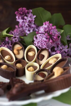 Bouquet of lilac flowers and chocolate candies with filling and nuts, chocolates with nuts on a plate, background. Sweets made of black, milk and white chocolate with hazelnuts, almonds and cashews 스톡 콘텐츠