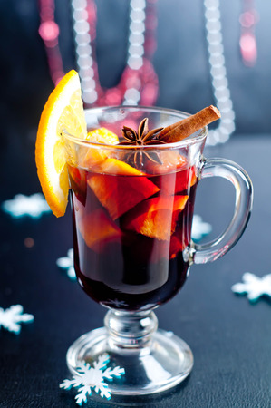 Hot red mulled wine isolated on white background with christmas spices, orange slice, anise and cinnamon sticks, close up. photo