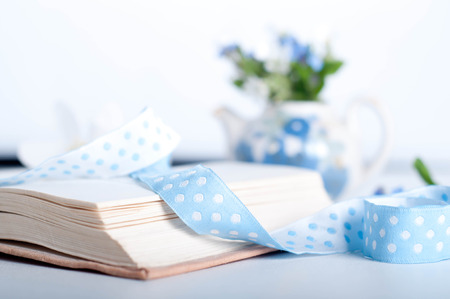 Books and wildflowers on napkin on wooden table on wooden wall  photo