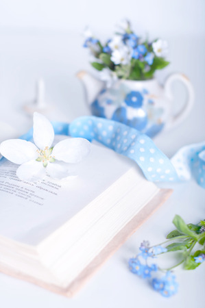 Books and wildflowers on napkin on wooden table on wooden wall background photo