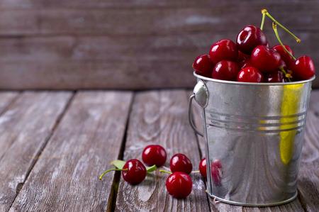 alimentacion sana: deliciosas cerezas frescas en la mesa de madera de color gris