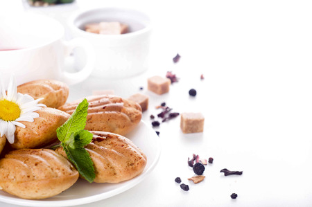 the madeleine: Madeleine homemade cakes in flower shape with tea on white background Stock Photo