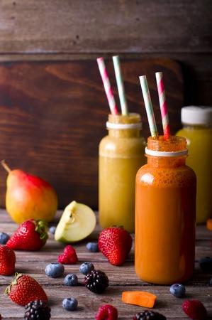 botella de plastico: Diferentes jugos y frutas en la mesa de madera sobre fondo