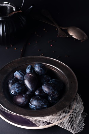 natural  moody: Fresh plums in natural light setting with moody vintage style