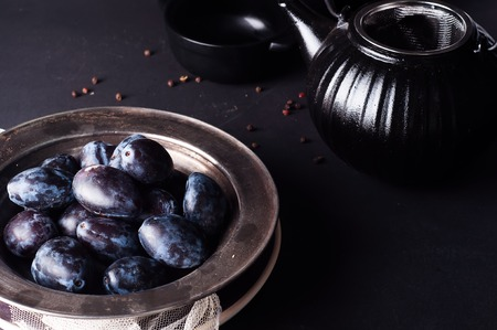 Fresh plums in natural light setting with moody vintage style