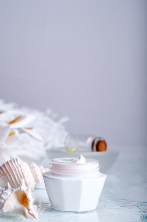 liniment: face cream on white background with seashells and flowers Stock Photo