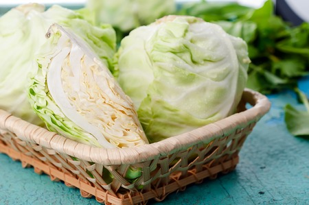 Head of cabbage and cut cabage on wooden board Standard-Bild