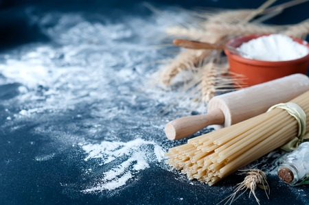 unboiled: Pasta spaghetti with flour on black background Stock Photo