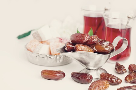 Traditional arabic tea set and dried dates. Isolated white background Stock Photo