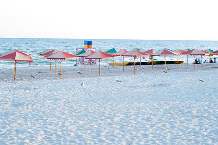 sun umbrellas: many sun umbrellas in the warm sandy beach of the tourist village Stock Photo