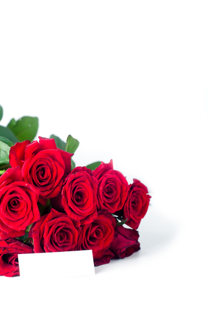 Card and red roses on white background