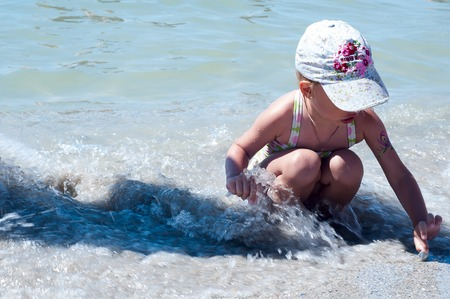 Adorable little girl playing with toy on beach vacation Stock Photo