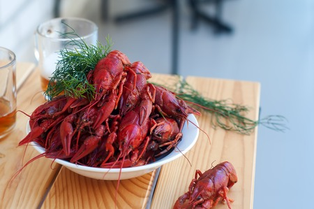 Boiled crayfishes with greenery on a plate in the table