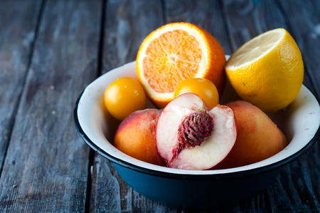 Fruits in plate on a wooden table: orange, lemon and peach Stock Photo