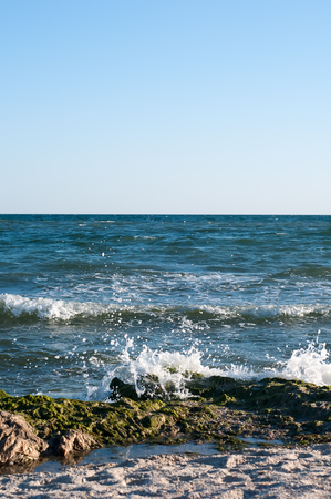 zenith: Big wave splashing. Sea water beating against the rocks and cliffs. Blue sky above the beach in the sun zenith refreshing drops of ocean water.