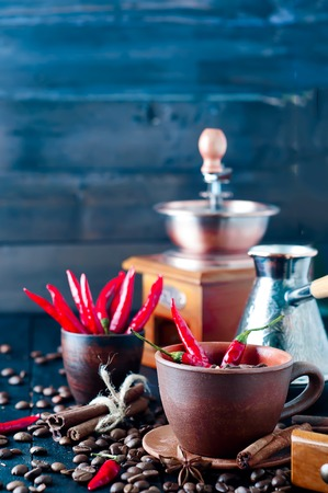 full bodied: Coffee beans in a cup of chili, cinnamon and Dittany on a dark wooden background coffee beans scattered around