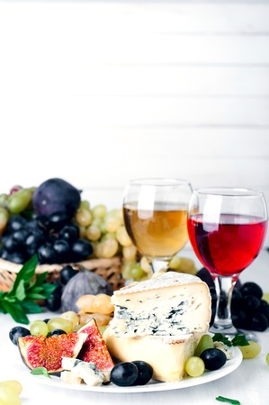 Grape, cheese and figs with a glasses of red and white wine on white background.