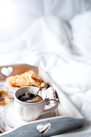 wooden tray with light breakfast on bed on the bed with white linen Stock Photo