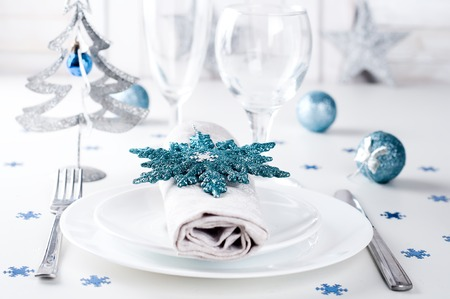 Christmas table setting in blue colors with fir tree and toys