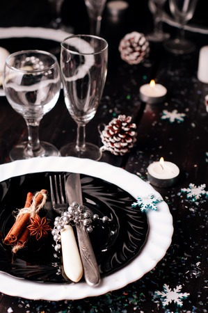 pinecones: Christmas table setting with pine cones and candles on a dark background . Holiday decoration