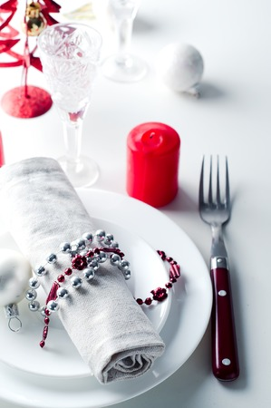 Christmas table setting in red with candles in white background