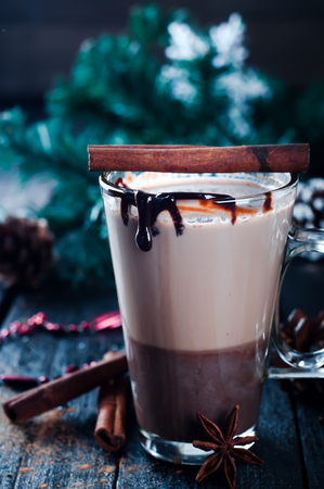 caramel coffee latte in a tall glass, wooden on dark background with Christmas decorations
