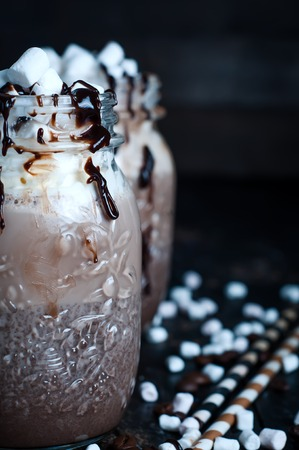 chocolate shake: Chocolate shake with dripping sauce and marshmallows on dark background