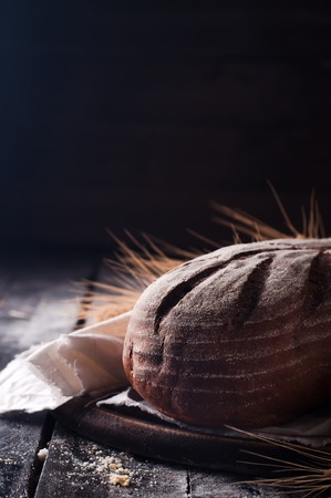 moody background: Rustic bread and wheat on dark wood table. Dark moody background with free text space. Stock Photo
