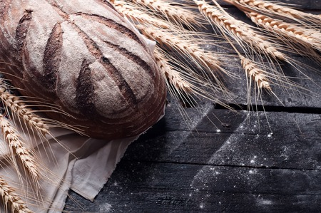moody background: Freshly baked traditional bread on wooden table. Dark moody background with free text space.