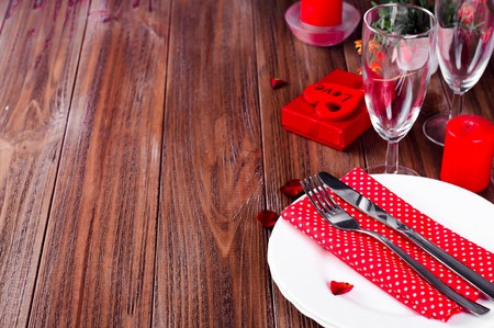 candle light table setting: Romantic Valentine Candle Light Dinner Table Setting with red roses, gift and burning candles against a brown background.