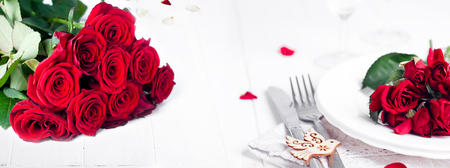 table decoration: Festive table setting with beige roses, wine glasses, napkins and cutlery, isolated