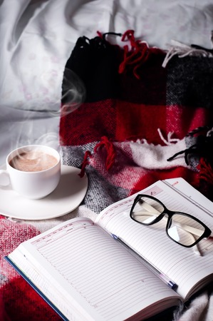 glases: Cup of cocoa staying on open book and glases on the bed with blanket, Good morning.