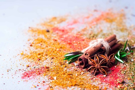cinnamon and anise on scattered spices on a concrete background