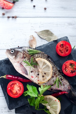 wine stocks: Raw fresh river fish fish on plate cutting board. Fish, lemon, tomato, herbs and spices. Top view with copy space on stone table