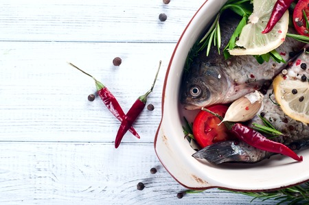 wine stocks: Ingredients for cooking healthy dinner. Raw uncooked river fish with vegetables, herbs and spices over rustic wooden background, clay container with copy space. Top view Stock Photo