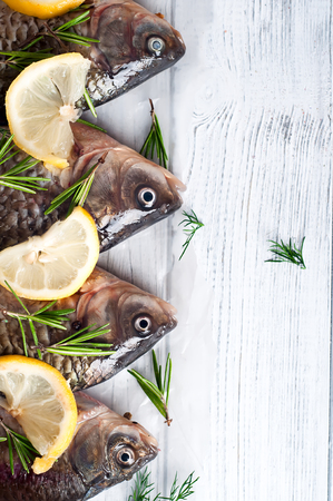 gilt head: Fresh river fishes with lemon on a wooden white background close up Stock Photo