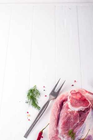 pancetta cubetti: piece of pork on a bone with spices on wood white background. Space for text