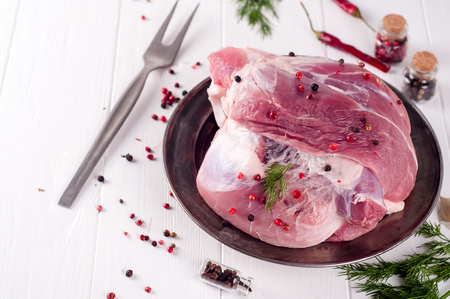 Raw juicy beef t-bone steak on an iron plate on the wooden table,