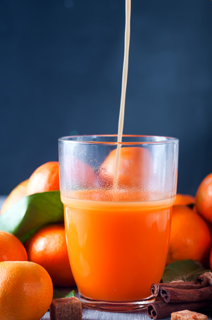 Healthy mandarin juice being poured into a glass, cinnamon sticks and tangerines on wooden table