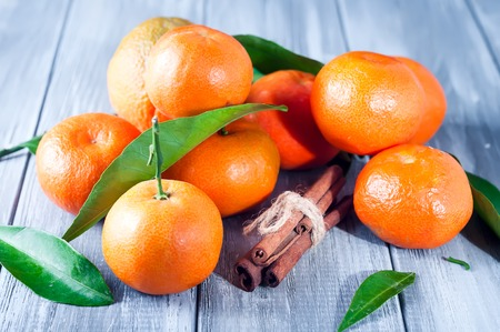 Tangerines with leaves and cinnamon on gray wooden table. Stock Photo