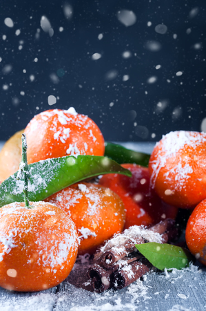 Tangerines with leaves, snow and cinnamon on gray wooden table.