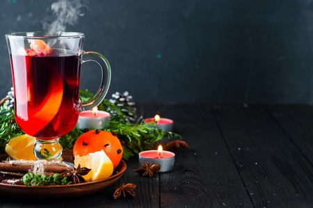 Mulled wine, mandarin, tree branch and spices on wooden background