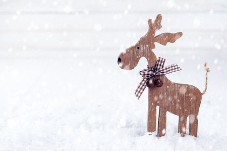 Christmas wooden deer on a background of white snow. Christmas card