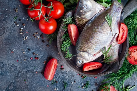 Food background for fish dishes cooking with various ingredients. Raw crucian with oil, herbs and spices on cutting board, top view.Healthy food or diet nutrition concept. Stock Photo