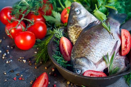 Voedsel achtergrond voor visgerechten koken met verschillende ingrediënten. Ruwe crucian met olie, kruiden en specerijen op de snijplank, top view.Healthy voedsel of dieet voeding concept.