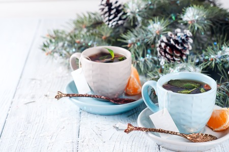 two tea cups and teabag and slices of mandarin on wooden white background with branches of fir tree and cones
