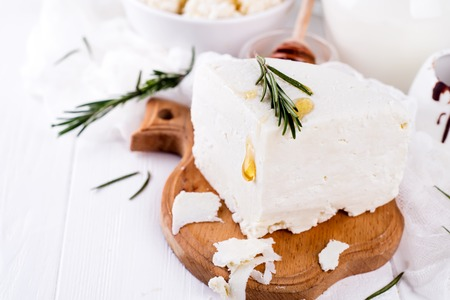 Fresh dairy products with rosemary and honey, white wood background,