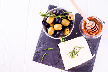 Adygei cheese with honey and olives on a concrete plate on a white wooden background Stock Photo