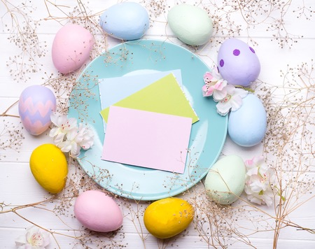 Pastel color easter eggs with a plate on white wooden bacgroung , copy space flat lay